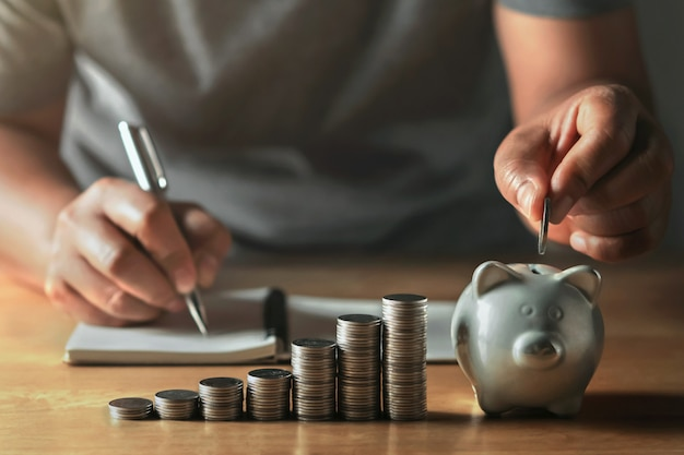 Saving money with hand putting coins in piggy bank concept financial