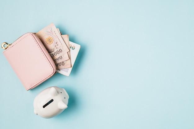 タイ通貨の財布、1000バーツ、ビジネスと金融の概念のための青い背景にタイのお金の銀行券で貯金箱を保存する