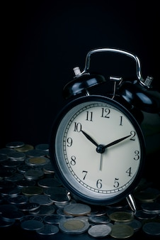 Saving time, alarm clock standing with coins isolated on black