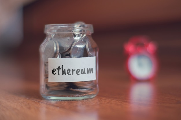 Savings concept for ethereum - glass jar with coins and inscription.