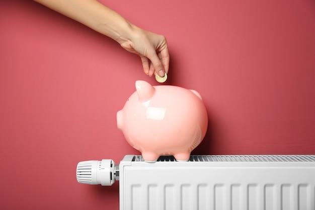貯蓄の概念。ピンクのスペースに温度調節器付きの暖房ラジエーターの上に立っている貯金箱にコインを入れる女性の手