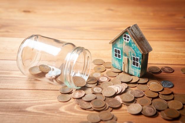 가정에 대한 저축 개념. 돼지 저금통에서 동전이 쏟아지고 그 위에 나무 테이블 위에 집이 있습니다.