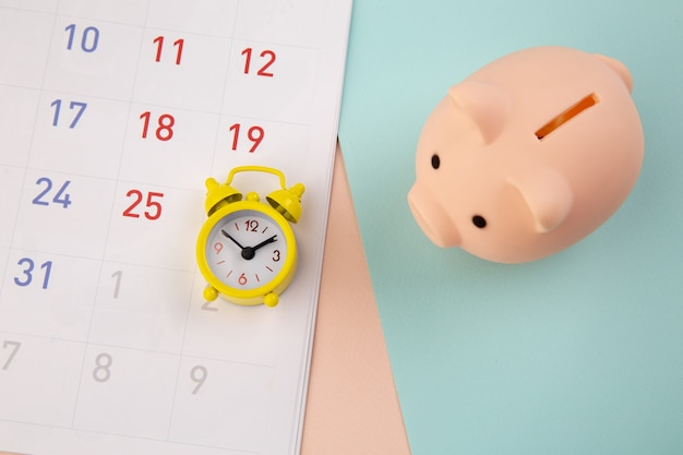 Savings concept. piggy bank and alarm clock with calendar on colorful background.
