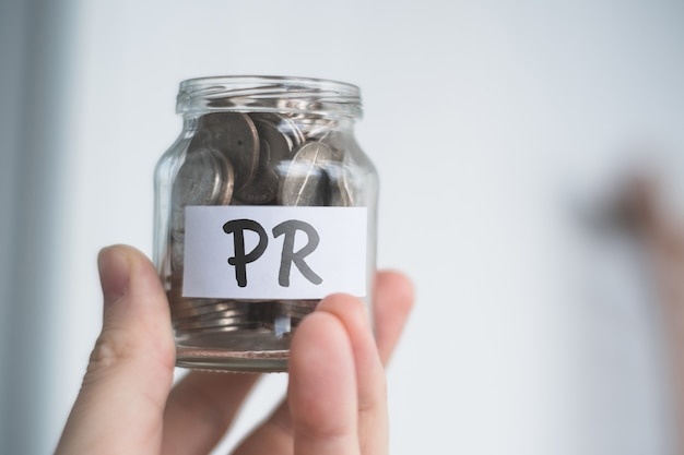 Savings concept for pr - glass jar with coins and inscription.