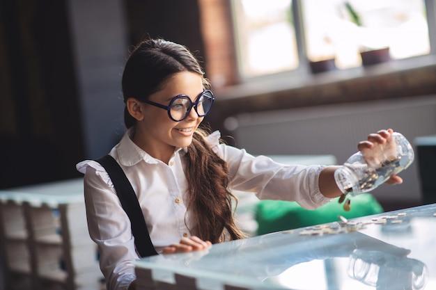 Экономия. темноволосая девушка держит банку с монетами и улыбается