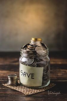 Накопление монет в прозрачной стеклянной бутылке