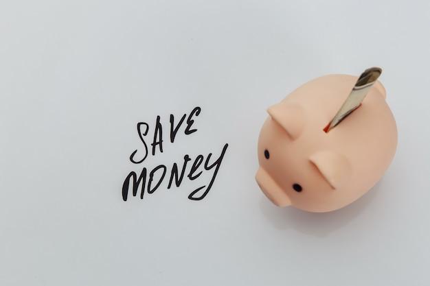 貯金箱の貯金と手書きのフレーズ「お金を節約する」。