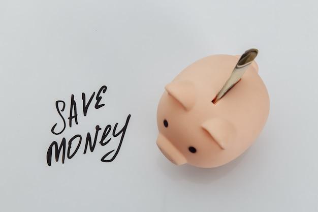 ピンクの貯金箱と手書きのフレーズ「お金を節約する」の節約。