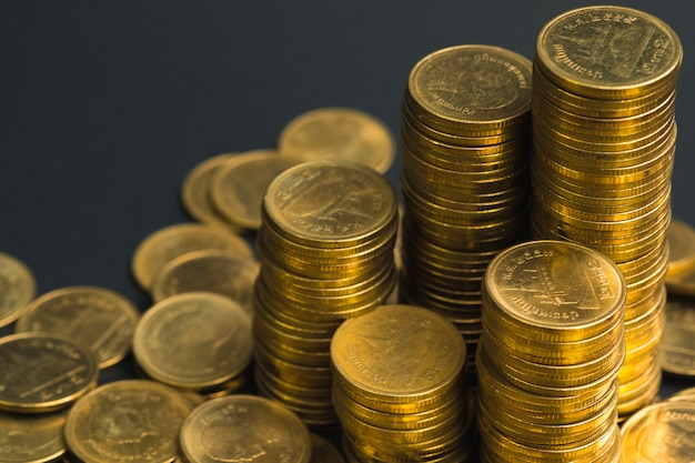 Savings, increasing columns of coins, piles of coins arranged as a graph in dark room, business banking concept.
