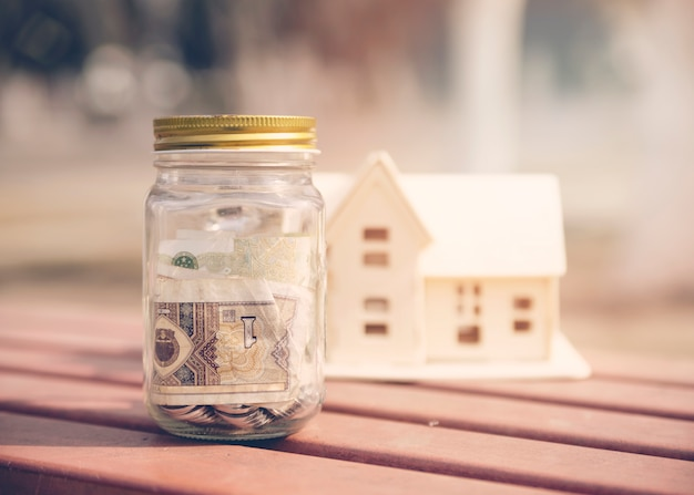 Savings jar with house miniature