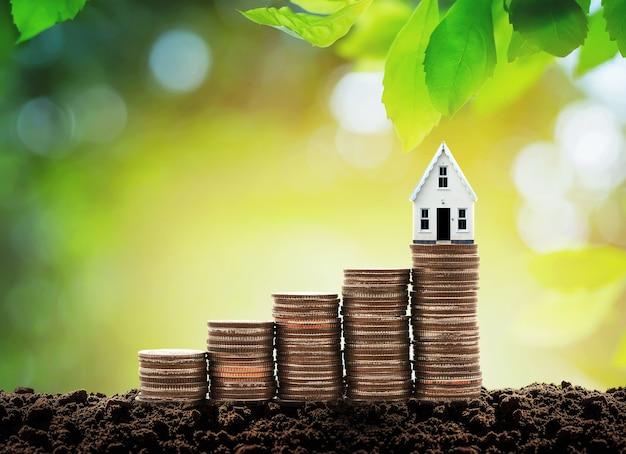 コインのスタック上のお金の成長の小さな家を節約するコインからお金の家