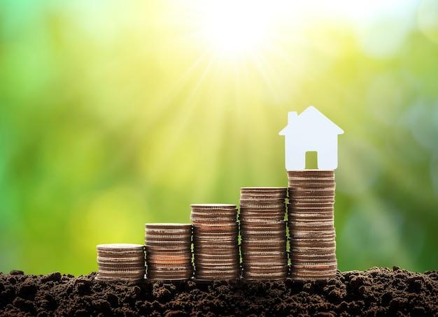 コインのスタック上のお金の成長の小さな白い家を節約するコインからお金の家