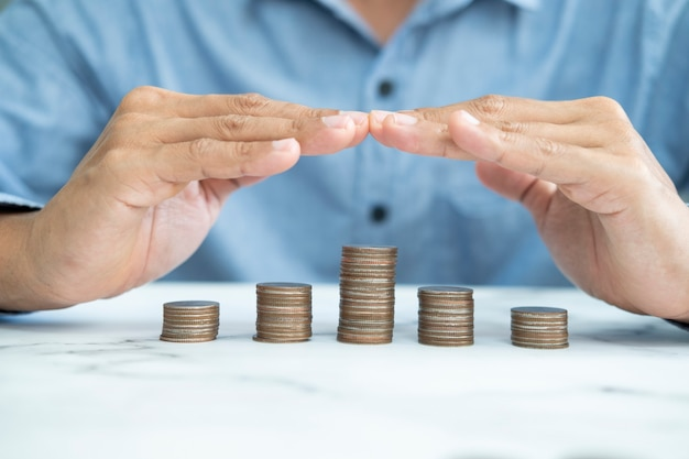 Savings protection, protect money, risk management, close up of male hands covering coins.