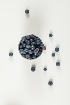 Savory blueberries in a mini bucket on white surface