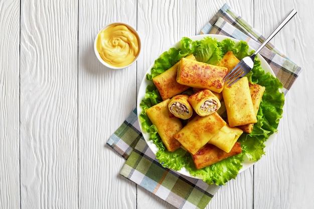 ひき肉とキノコを詰めたおいしいクレープロールは、白いプレートの新鮮なレタスの葉の悪いものに添えられます