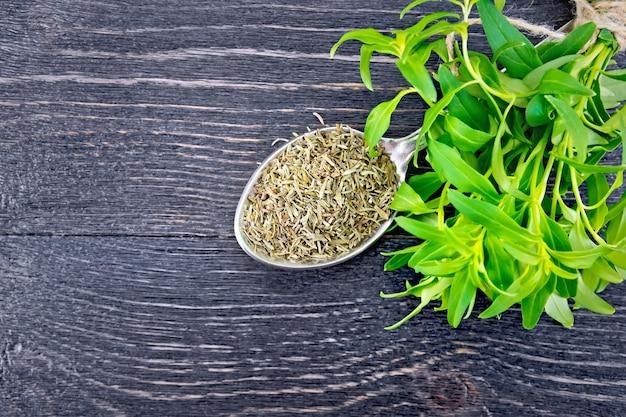 金属のスプーンで香ばしく乾燥し、木の板を背景に新鮮なハーブの束を上に