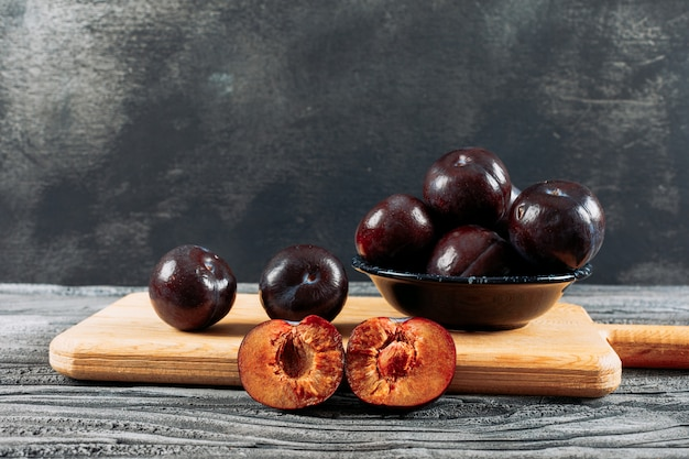 Savory plums in a dish and wooden board on a white wood and dark grey background. side view.