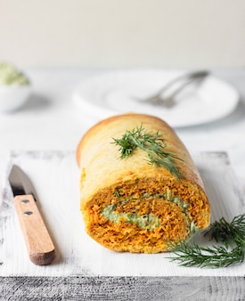 Savory pumpkin or carrot roll with cream cheese, avocado and salmon. gluten free.