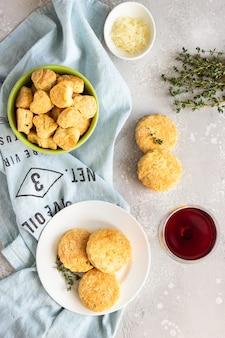 화이트 세라믹 접시에 치즈와 백 리 향 짭짤한 스콘 또는 쿠키.