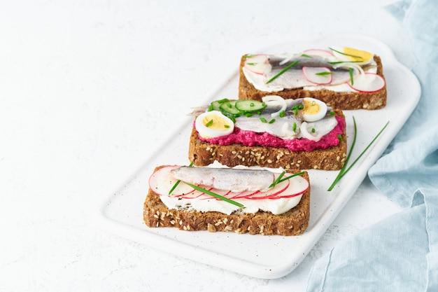 Пикантный сморреброд, набор традиционных датских сэндвичей. черный ржаной хлеб с анчоусом