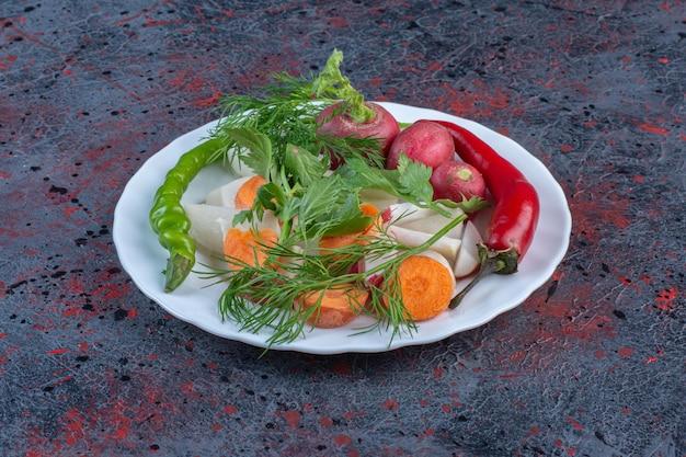 暗い色の背景に白い大皿においしい野菜ミックス。高品質の写真