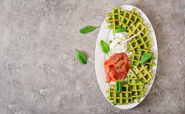 Waffle salati con spinaci e crema di formaggio, salmone in zolla bianca. cibo gustoso. vista dall'alto. disteso