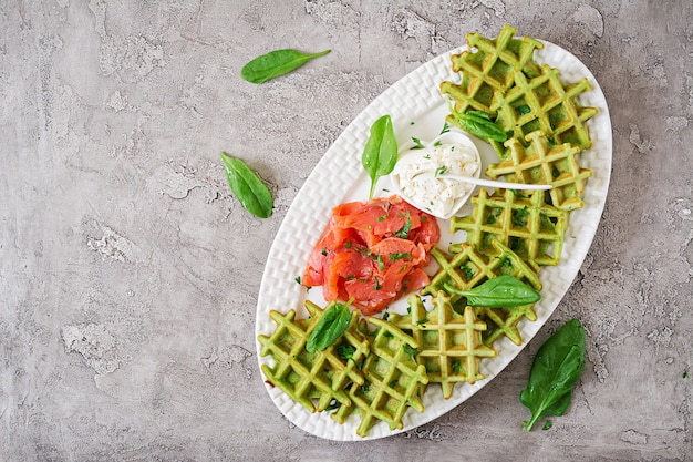 Savory waffles with spinach and cream cheese, salmon in white plate.