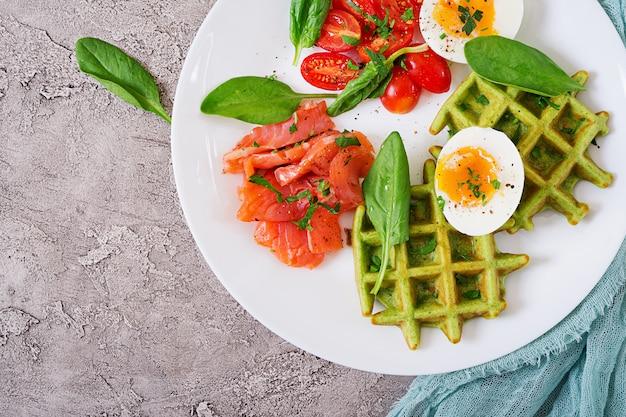 Waffle salati con spinaci e uovo, pomodoro, salmone in zolla bianca. cibo gustoso. vista dall'alto. disteso