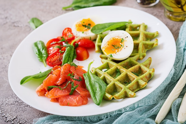 Savory waffles with spinach and egg, tomato, salmon in white plate.