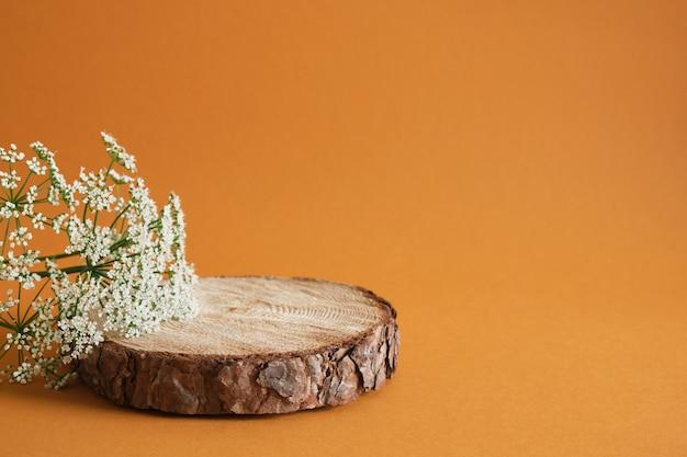 あなたの製品の茶色の背景の表彰台として木のカットを見た、装飾のための花