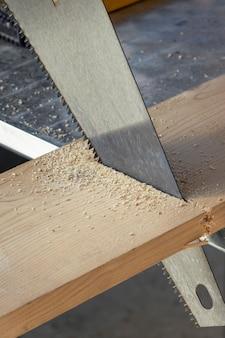 Saw cutting through a board. wood workshop.