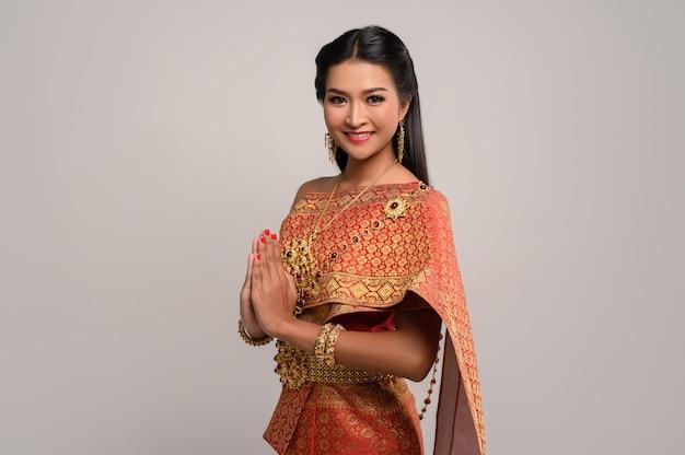 Женщины, носящие тайскую одежду, которые уважают, символ sawasdee