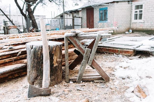 Пила в зимнем дворе. русская зима. место для колки дров. холодные, ранние заморозки, иней концепция