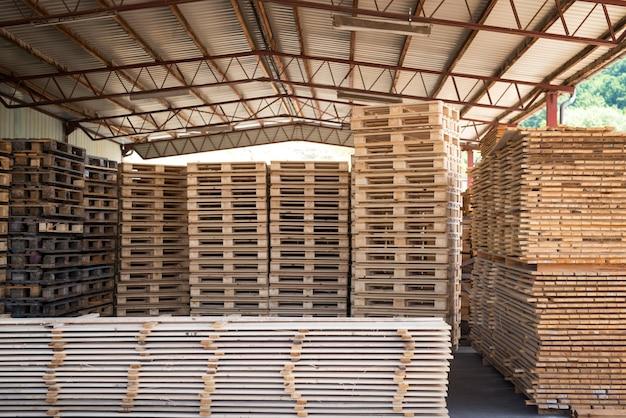 팔레트와 목재 재료 널빤지의 더미와 함께 제재소 공장 창고.