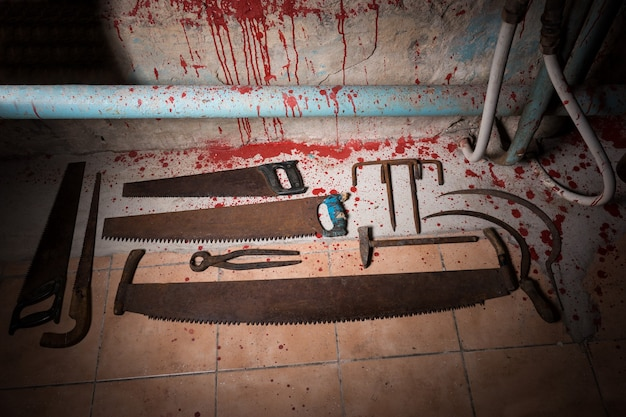 Saws, tongs and other devices on the bloody floor  in basement with pipes and wires in a halloween horror concept