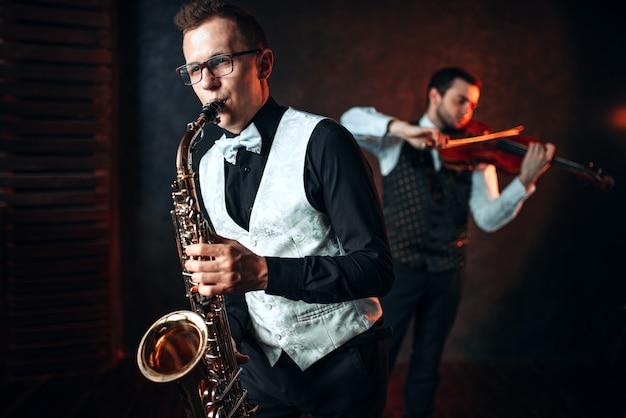 Дуэт саксофона и скрипача играет классическую мелодию. джазмен и скрипач