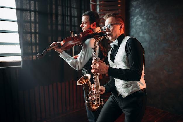 Дуэт саксофона и скрипача играет классическую мелодию
