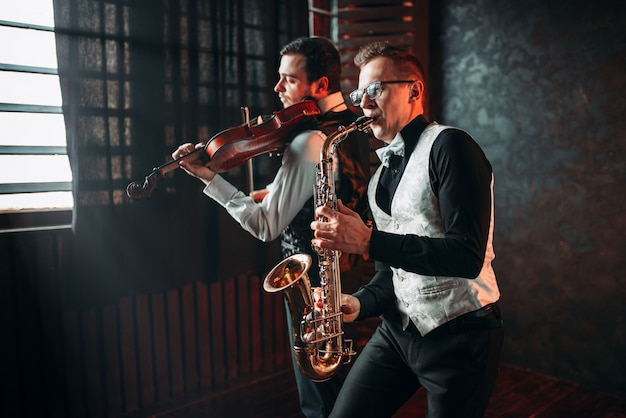 Sax man and fiddler duet playing classical melody