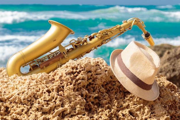 Саксофон и шляпа на скале на фоне морских волн.