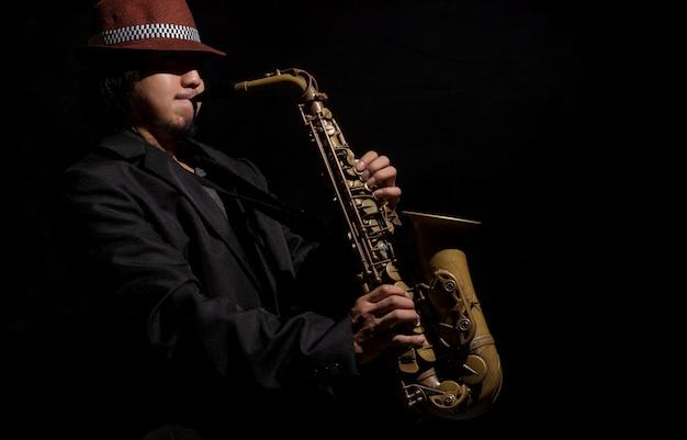 A saxophone player in a dark background