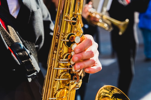 Saxophonist fingers playing a piece during a street festival.