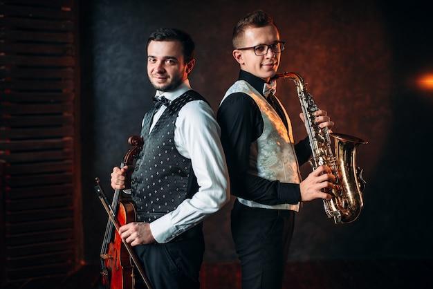 Саксофонист с саксофоном и скрипка со скрипкой музыкальный дуэт. джазмен и скрипач