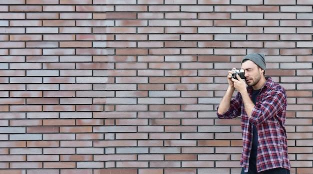 チーズ、レトロなカメラを持っている流行に敏感なファッション写真家の男と言います。全景。コピースペース