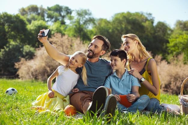 Скажите сыр. вдохновленный, хорошо сложенный мужчина улыбается и делает селфи со своей семьей на открытом воздухе.