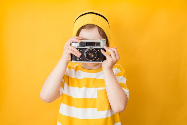 Say cheese. young active kid boy takes photo with retro camera, poses against yellow background, has awesome trip, explore new places
