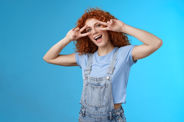 こんにちは夏をチーズと言います。陽気で魅力的な遊び心のあるカリスマ的な赤毛のかわいい女の子の巻き毛の髪型は、舌の平和の勝利のジェスチャーの目がおかしな態度の幸せな感情を模倣してうれしそうに頭を傾けます。