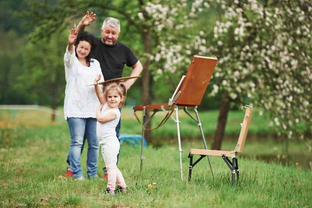 Поздоровайтесь с фотографией. бабушка и дедушка веселятся на природе с внучкой. концепция живописи