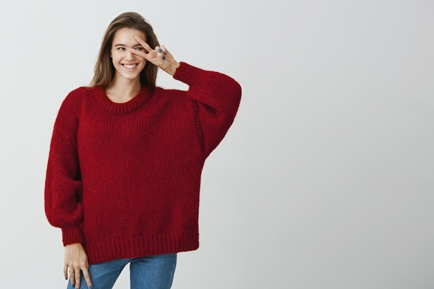 Say hi to new opportunities ahead. studio shot of good-looking happy woman in trendy loose sweater holding v sign over eye and smiling broadly, being in playful and flirting mood