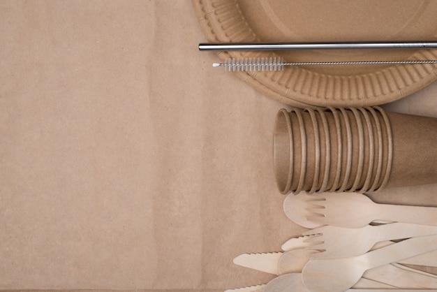プラスチックにノーと言ってください。木製のカトラリー、紙コップとプレート、およびクラフト紙の背景テーブルで隔離された右側に配置された金属ストローの俯瞰写真の上の上部