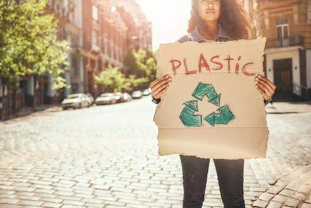 서 있는 동안 플라스틱이라는 단어가 적힌 간판을 들고 있는 플라스틱 젊은 여성 운동가에게 아니오라고 말하세요